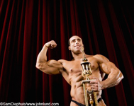 Handsome smiling fit body builder holding a big trophy on stage for winning the body building competition. The man is flexing one of his biceps and has an amazing physique.